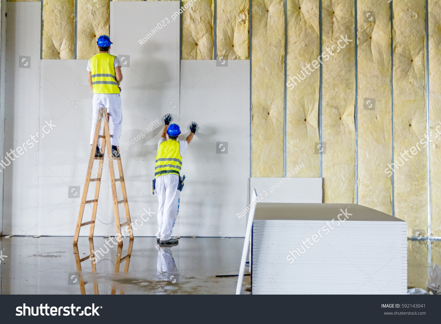 stock-photo-workers-are-assembly-gypsum-wall-plasterboard-is-under-construction-using-wooden-ladder-592143041 (1)